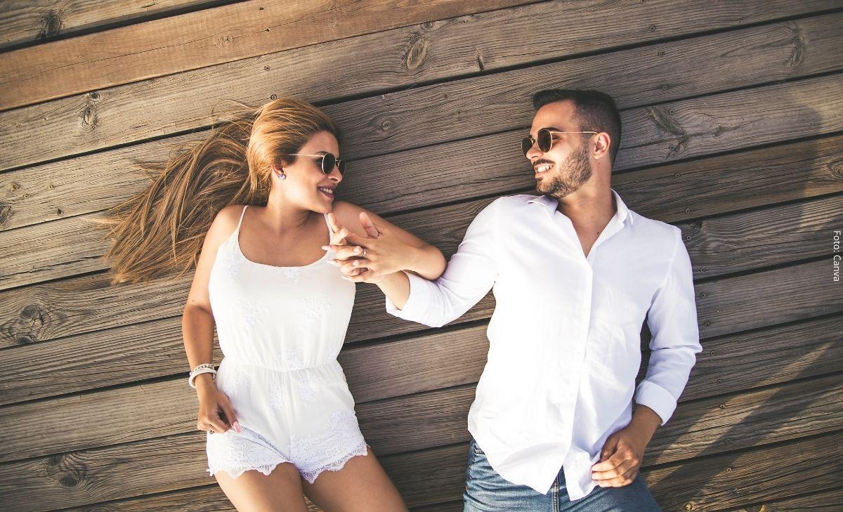 Foto de una pareja tomada de la mano recostados en el piso