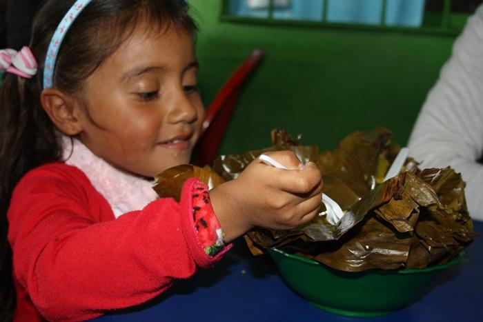 Foto de una niña comiendo tamal