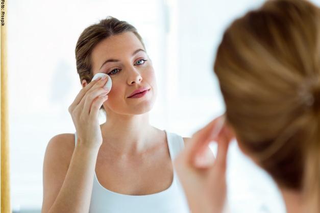 la mujer joven hermosa esta limpiando su cara mientras que mira en el espejo en el cuarto de bano 1301 7996