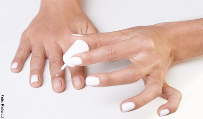 Manos de mujer con esmalte blanco