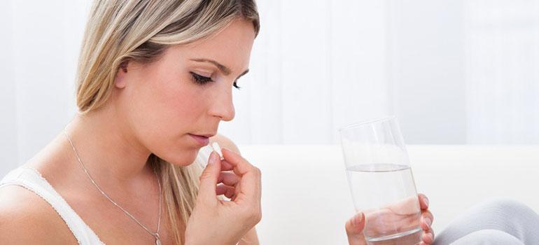 Mujer tomando pastillas anticonceptivas