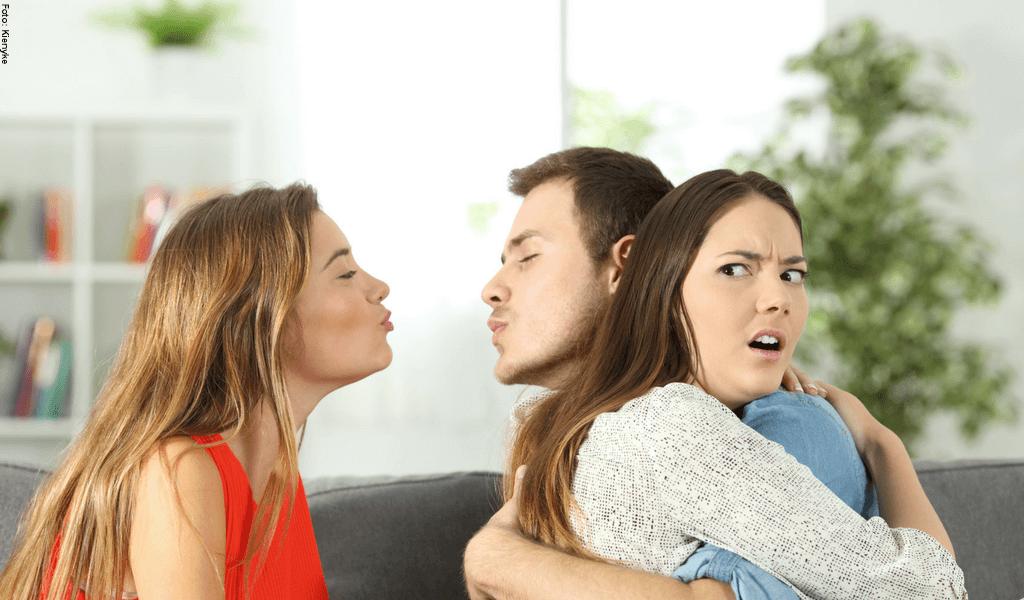 Mujer abrazando a un hombre, mientras él intenta besar a otra mujer.