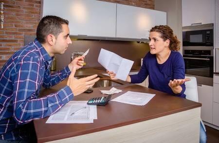 Una mujer y un hombre discutiendo por el dinero con papeles y calculadora encima de la mesa