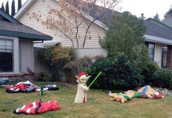 Figura de Yoda en un Jardín rodeado de Papá Noeles desinflados