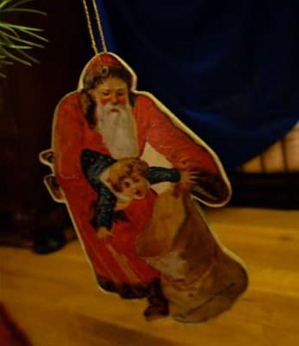 Adorno de arbolito navideño que muestra a San Nicolás metiendo un niño en una bolsa