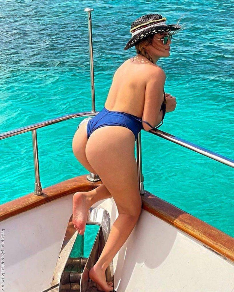 Foto de Veronica, la hermana de Karol G de espalda con un vestido de baño azul sobre un yate