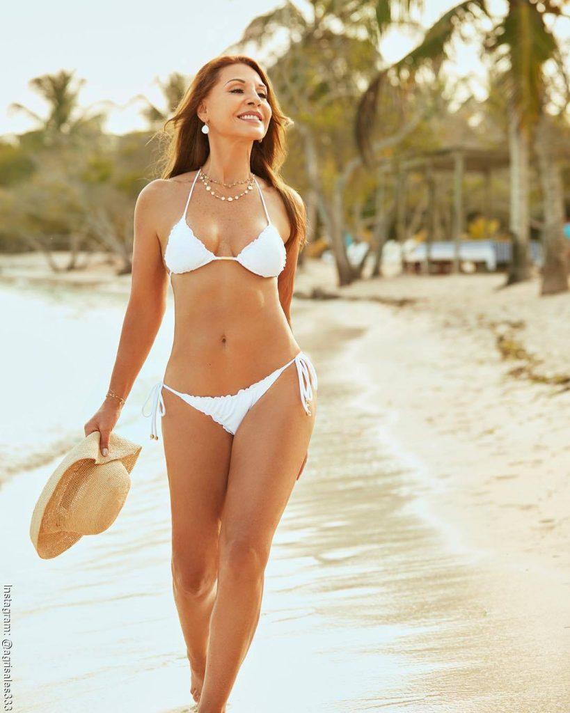 Foto de Amparo Grisales caminando por la playa con un bikini blanco
