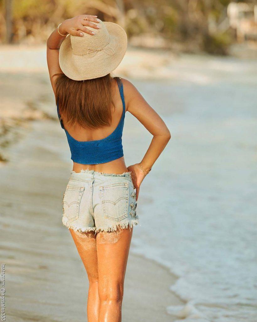 Foto de Amparo Grisales caminando por la playa con un sombrero y pantaloneta de jean