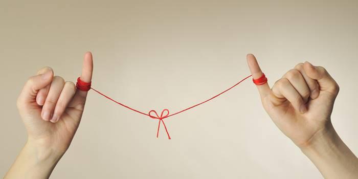 Foto de dos manos unidas por un hilo rojo