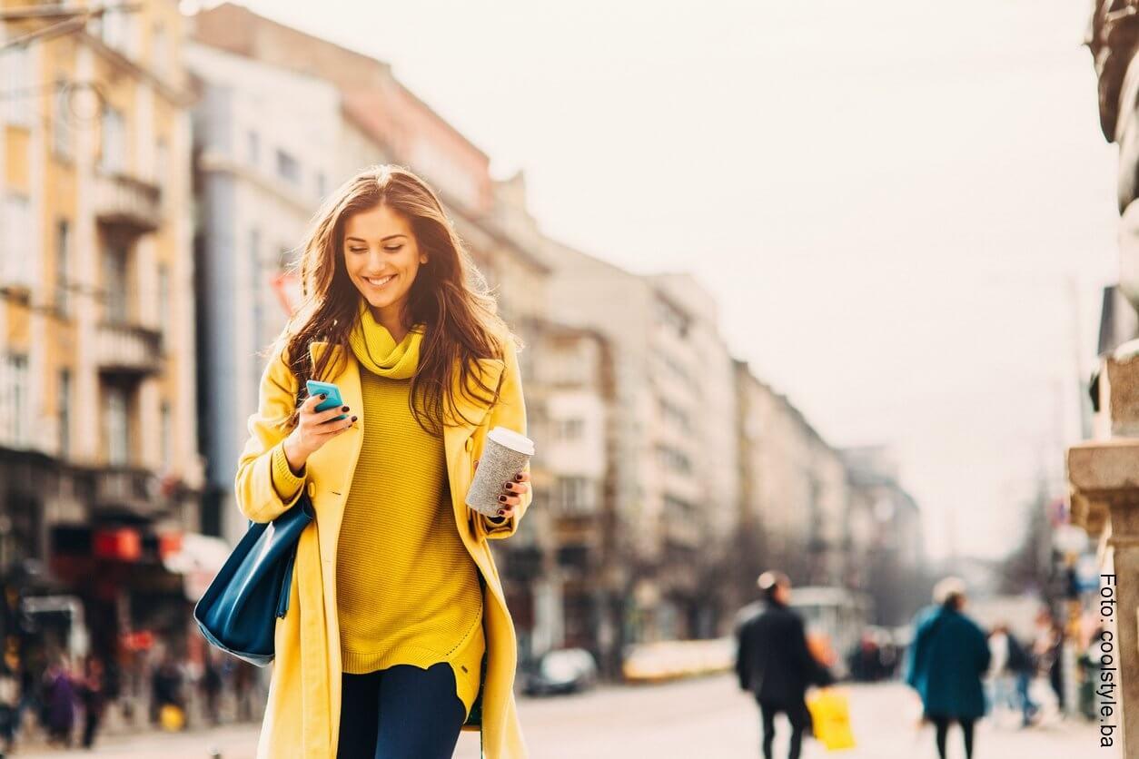 Mujer caminando por la calle con un celular en la mano