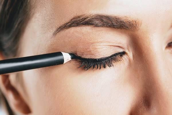 Foto de una chica poniéndose lápiz de ojos