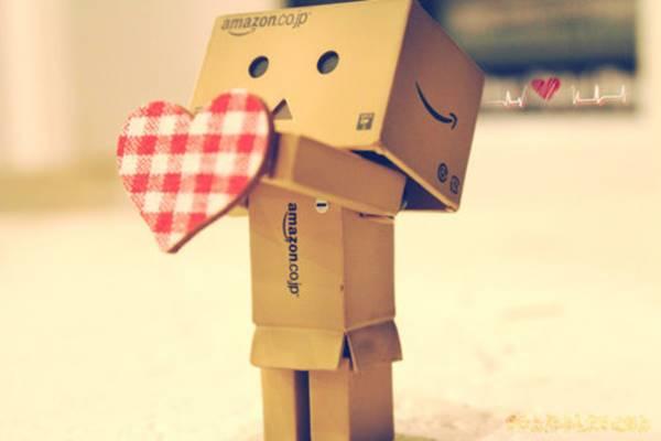 Foto de muñeco de cartón con corazón en las manos