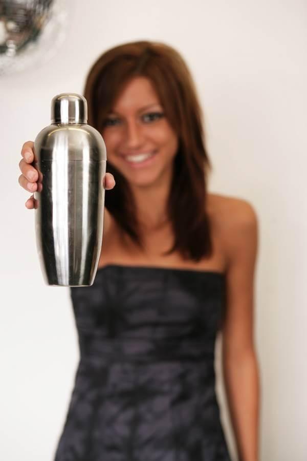 Foto de una chica con una coctelera en la mano