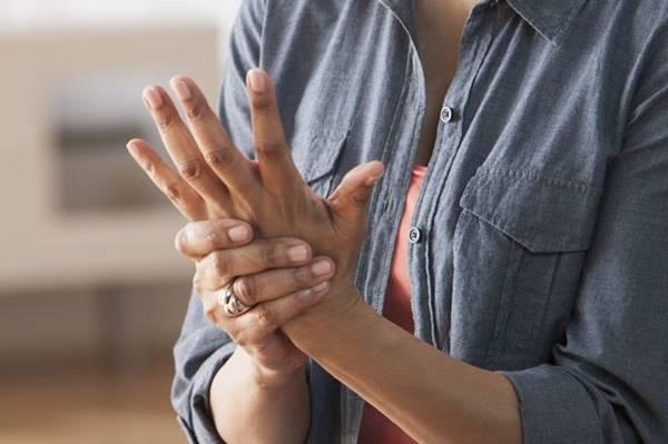 Foto de una mujer sobándose la mano adolorida