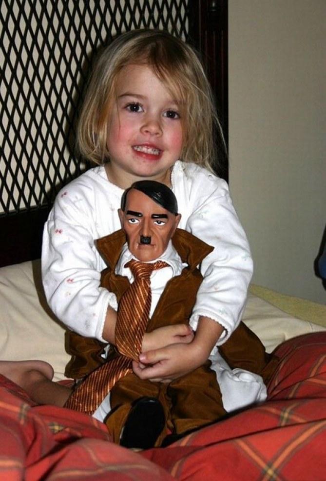 Foto de una niña con un juguete de Hitler.