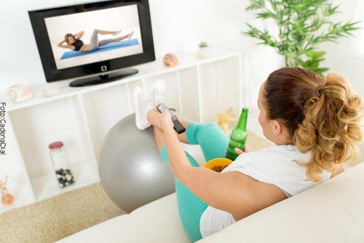 mujer joven sin ejercitarse viendo tv