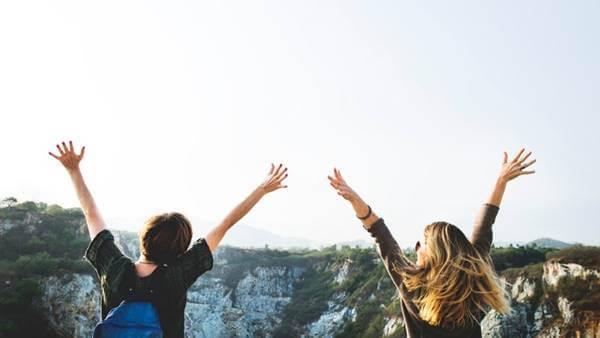Foto de una pareja con los brazos extendidos hacia arriba