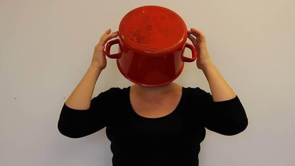 Foto de una mujer con una olla sobre la cabeza