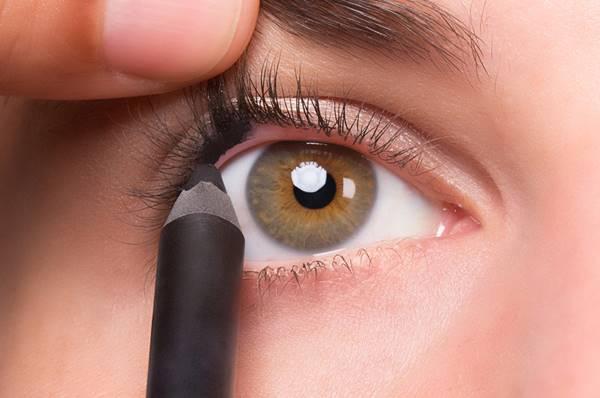 Foto de chica plicando delineador en el ojo