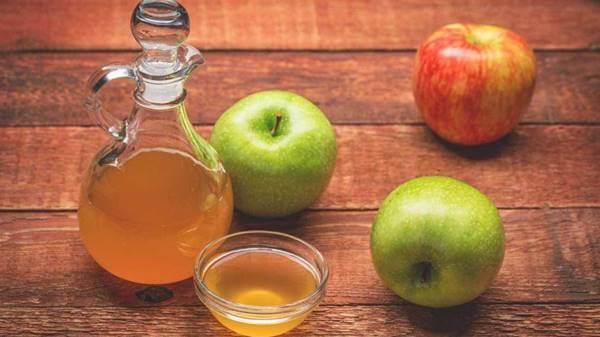 Foto de una botella de vinagre y manzanas