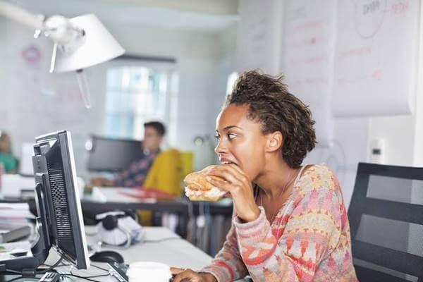 Foto de una chica comiendo hamburguesa en la oficina