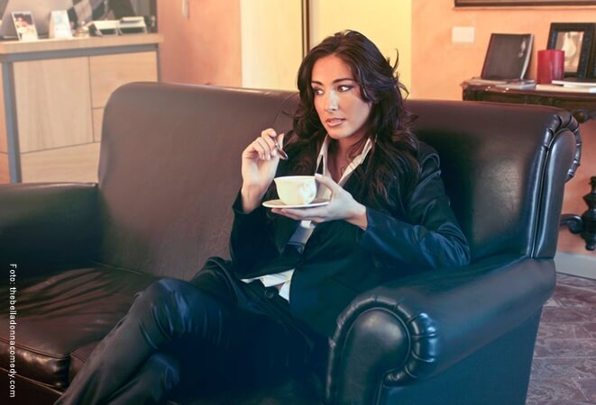 Mujer tomando café en el sillón.