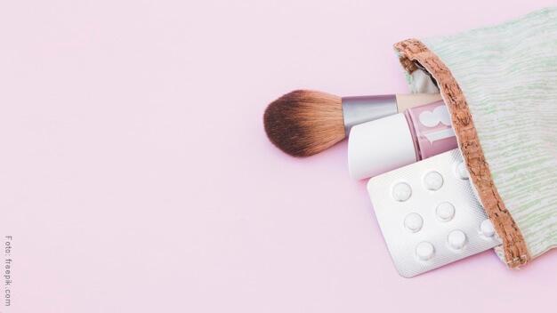 Bolsa de maquillaje y pastillas anticonceptivas en el bolso de mano.