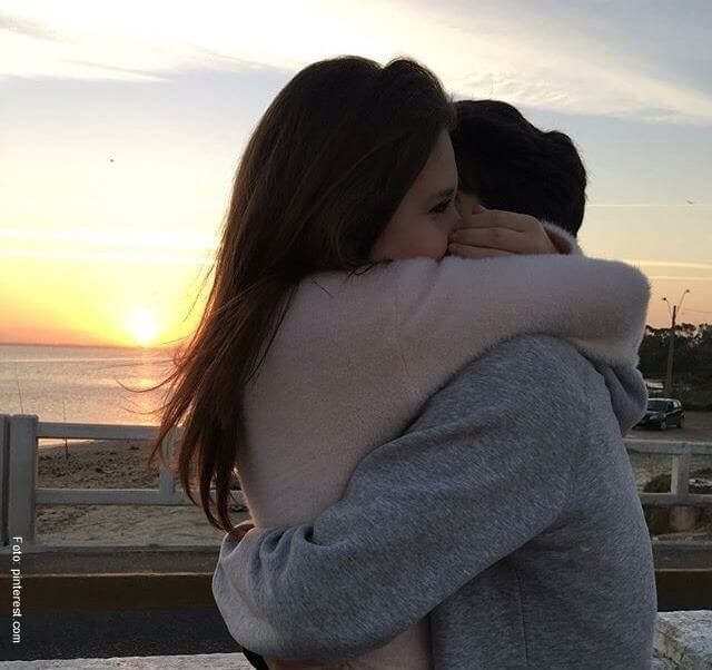 Pareja abrazándose frente al mar.