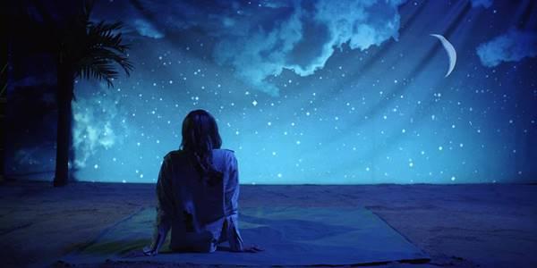 Foto de una chica sentada viendo una imagen de la noche