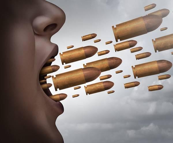 Foto de una persona con balas saliendo de su boca como palabras