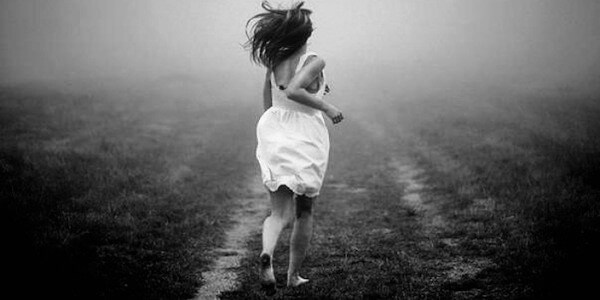 Foto de una chica corriendo descalza en el campo