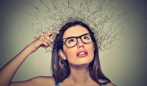 Foto de una mujer tocándose la cabeza y mirando hacia arriba