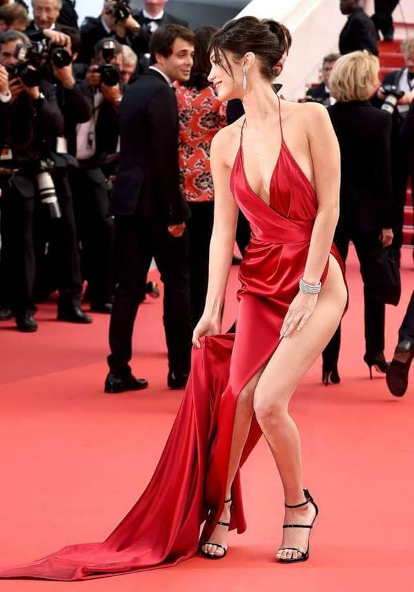 Foto de Bella Hadid arreglándose la falda que se le rompió por la abertura y casi la dejó en bola