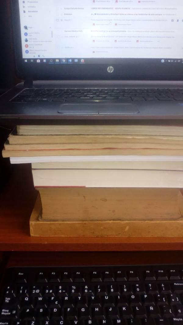 Foto de un computador sobre una pila de libros