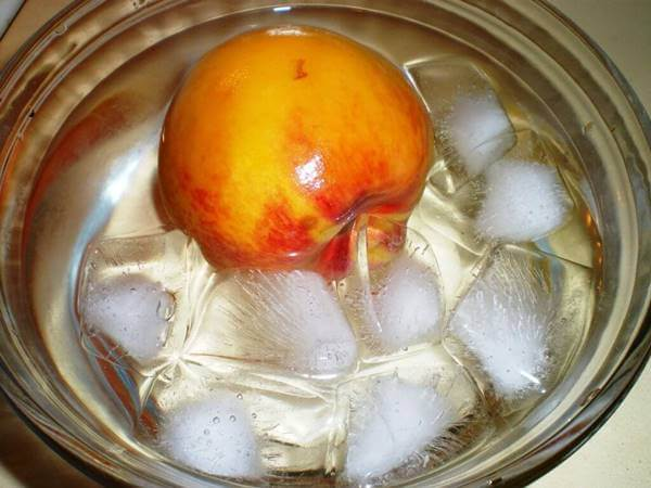 Foto de un durazno dentro a agua con hielo