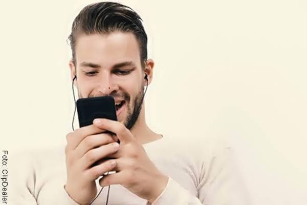 Foto de un hombre emocionado mirando su celular