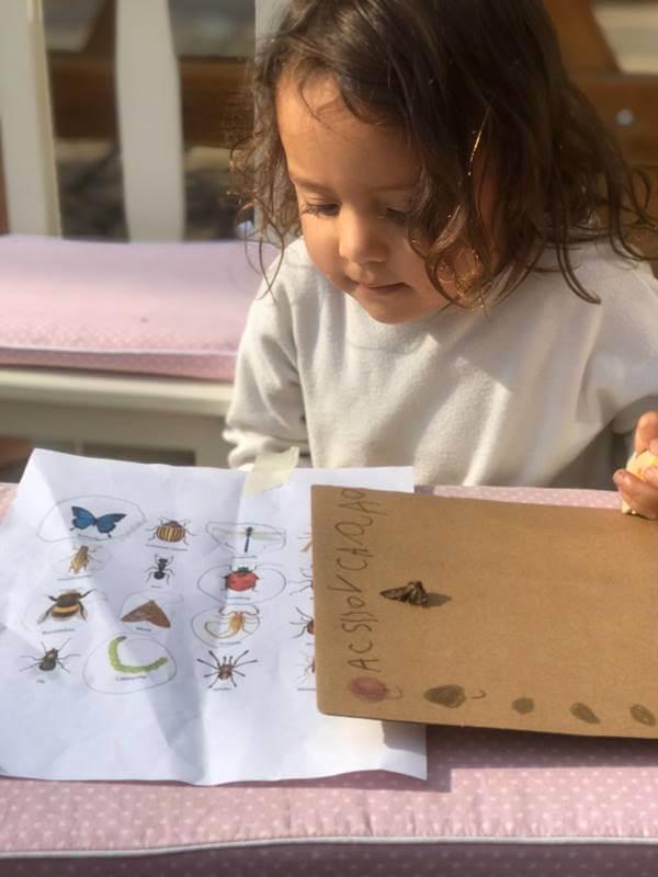 Foto de una niña jugando con insectos y dibujos