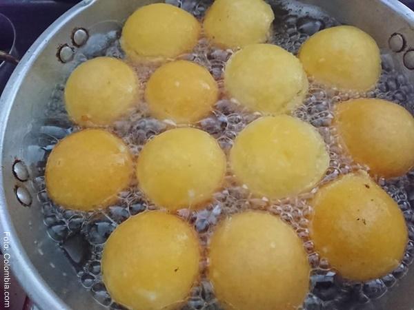 Foto de algunos buñuelos en aceite caliente en un sartén
