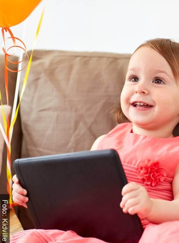 Foto de una niña con una tablet y globos