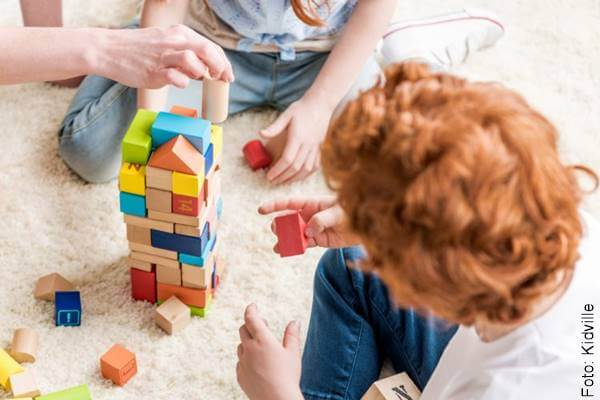 Foto de unos niños armando una torre con cuadritos de madera