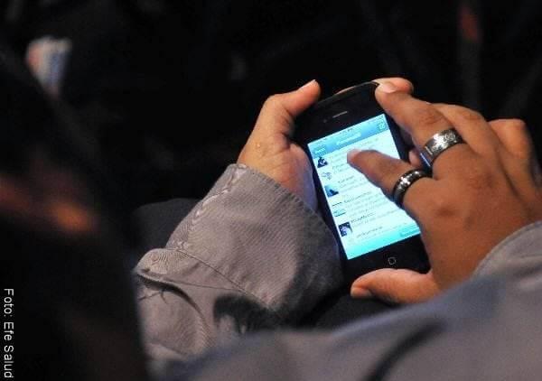 Foto de un hombre mirando una conversación en su celular