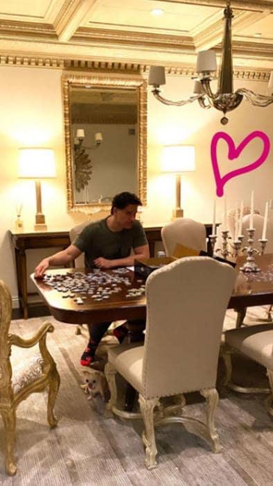 Joe Manganiello, esposo de Sofía Vergara, posa con su nuevo look en el comedor de su casa mientras realiza un rompecabezas.