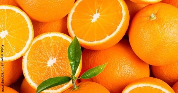 Foto de unas naranjas partidas por la mitad con hojas verdes