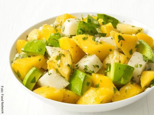 Foto de ensalada de aguacate, piña, melon en un recipiente blanco