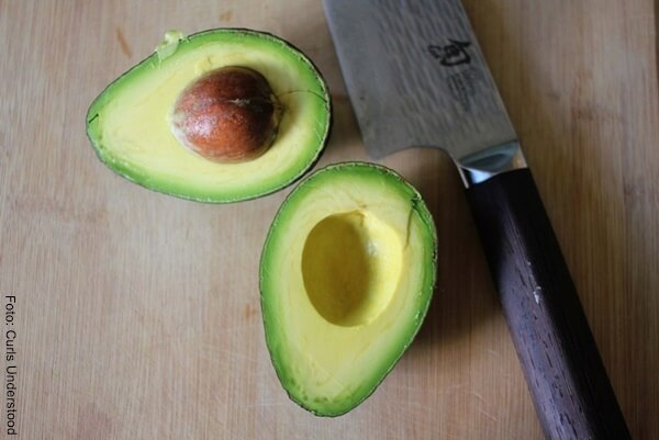 Foto de un aguacate partido por la mitad con un chuchillo de mango negro