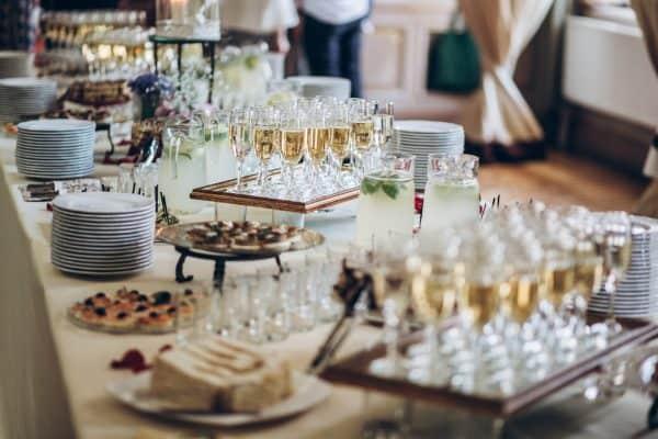 Foto de una mesa con copas de champaña, platos elegantes y postres
