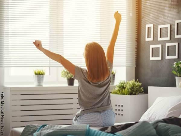 Foto de una chica desperezándose en la cama para ilustrar las razones para amar el mañanero