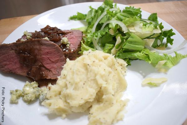 Foto de puré de papa, ensalada y carne en un plato grande color blanco
