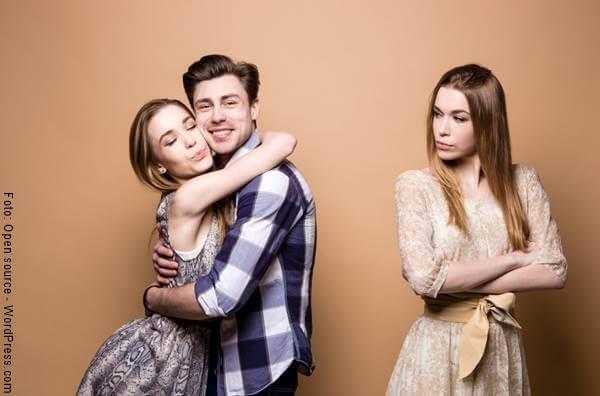 Foto de una mujer celosa mirando a una pareja abrazada
