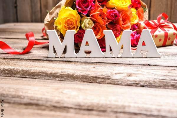 Foto de la palabra mamá con flores y un regalo atrás